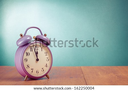 Retro violet alarm clock on desk front mint green wall background - stock photo