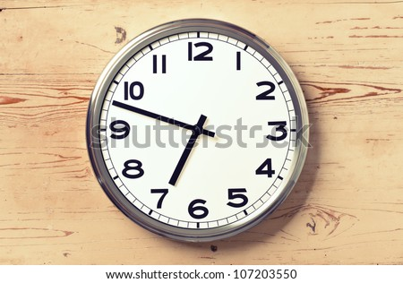 retro wall clock on old wooden background - stock photo