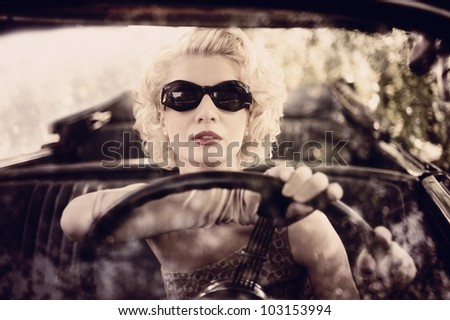 Retro woman behind steering wheel - stock photo
