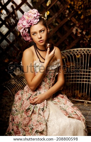 Retro woman. Girl in vintage style with flowers in hairstyle - stock photo