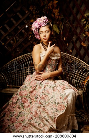 Retro woman. Girl in vintage style with flowers in the hairstyle - stock photo