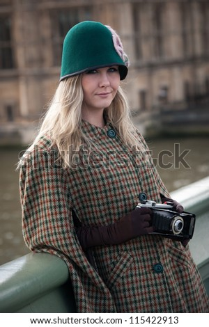 Retro woman in London city,with vintage camera , Westminster bridge