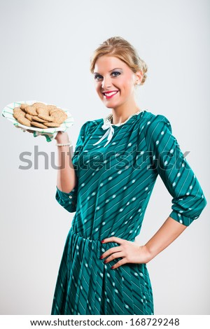 Retro woman is showing what a delicious cookies she has made,Delicious cookies for you - stock photo