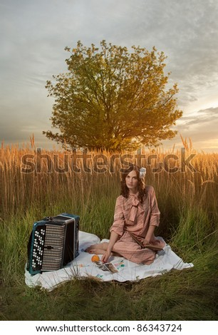 Retro woman seating with an accordion, book and pen, in a field of tall grass.