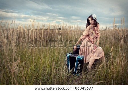 Retro woman sitting with an accordion, in a field of tall grass.