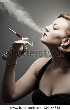 Retro woman smoking a cigarette - stock photo