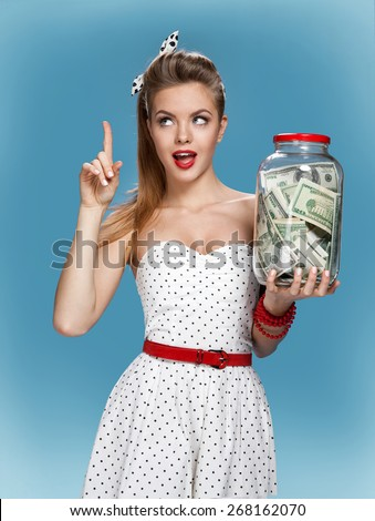 Retro woman with a jar of money having an idea How to Spend Money. Shopping concept / photo set of young American pin-up model on blue background - stock photo