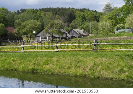 Retro wooden European village on lake bank spring landscape - stock photo