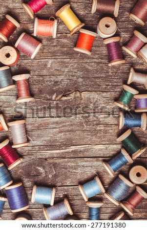 Retro wooden sewing spools with colourful threads over vintage wooden background - stock photo
