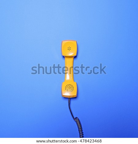 Retro yellow telephone tube on blue background - Flat lay