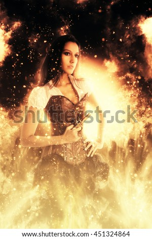 Retro young woman wearing a sexy bustier standing with her hand on her hips holding a gun engulfed in flames and fiery sparks looking to the right of the frame in a conceptual image - stock photo