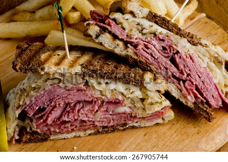 Reuben Sandwich on grilled rye bread, corned beef, Swiss cheese, sauerkraut and topped with thousand island dressing - stock photo