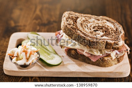 reuben sandwich with kosher dill pickle and coleslaw on wood plank - stock photo