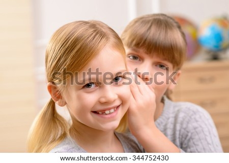 Reveal the secret. Pleasant nice little girls smiling and gossiping while having fun together