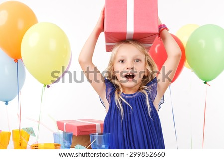 Revel in birthday atmosphere. Pleasant young girl holding present on her head  - stock photo