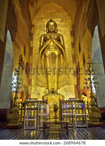 Revered standing Buddha statue in the ancient Ananda temple in Bagan, Myanmar (Burma). - stock photo