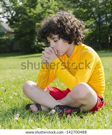 Reverence and praise of a young Latin boy to his Creator in Heaven. - stock photo