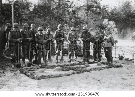 Reverent German soldiers stand with shovels at the grave of the commanding officer. They are with a reconnaissance unit in the woods of Dzuskawcza, Soviet Union during operation Barbarossa. - stock photo