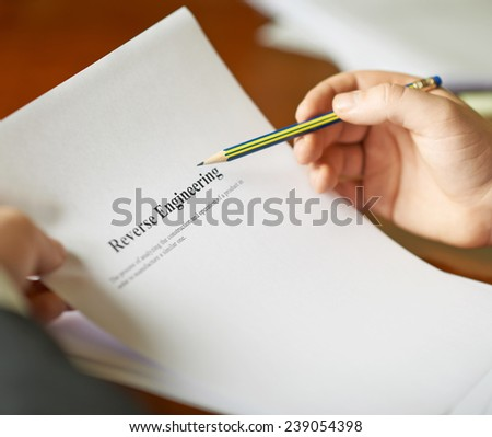 Reverse Engineering definition as a shallow depth of field close-up composition of a man in a business suit working with the text - stock photo