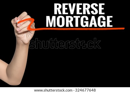 Reverse Mortgage word write on black background by woman hand holding highlighter pen - stock photo
