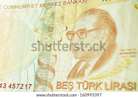 Reverse of a five Lira banknote from Turkey showing the renowned historian of science Aydin Sayili (1913-1993). Used banknote photographed at an angle.