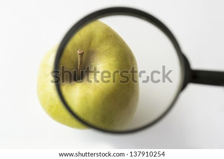 reviewing an apple with a magnifying glass - stock photo