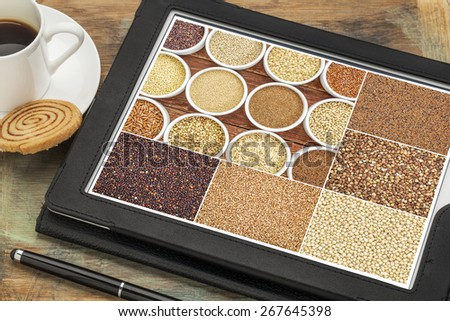 Reviewing pictures of healthy gluten free grains (quinoa, kaniwa, brown rice, millet, amaranth, teff, buckwheat, sorghum) on a digital tablet. All screen pictures copyright by the photographer. - stock photo
