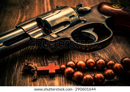 Revolver and a rosary on the wooden table. Focus on the rosary. Close up view, image vignetting and the orange-blue toning - stock photo