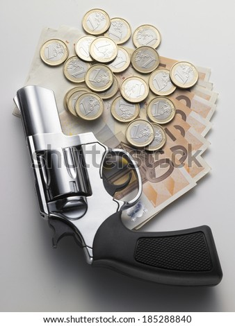 revolver and euro coins on white background - stock photo