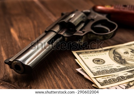 Revolver and money on the wooden table. Close up view, focus on the dollars - stock photo
