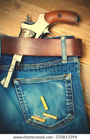 revolver in his belt of old blue jeans and a few yellow cartridges. instagram image filter retro style - stock photo