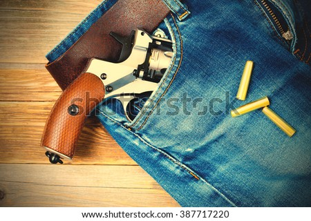 revolver in the pocket of blue jeans. instagram image filter retro style - stock photo