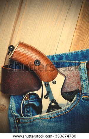 revolver in the pocket of old blue jeans. instagram image filter retro style - stock photo