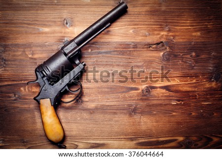 Revolver on the wooden table - stock photo