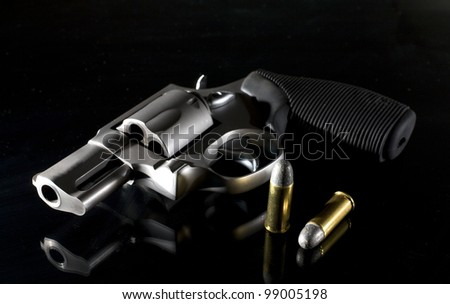 Revolver that is on a black background with side lighting - stock photo