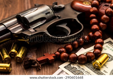 Revolver with cartridges and a rosary on the wooden table. Close up view - stock photo