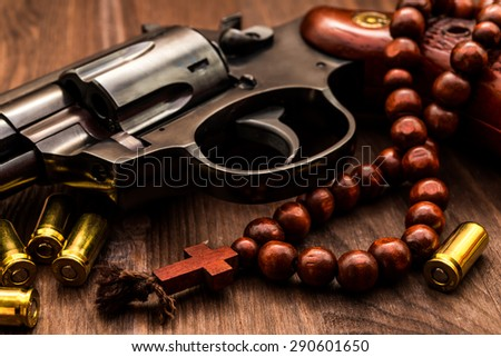 Revolver with cartridges and a rosary on the wooden table. Focus on the rosary. Close up view - stock photo