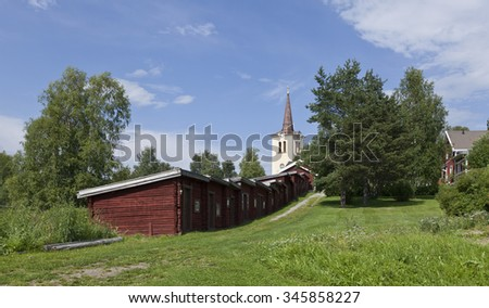 REVSUND, SWEDEN ON AUGUST 07. View of the Falu red painted cabins, yellow church tower on August 07, 2015 in Revsund, Sweden. Sunny summer day, green lawn and trees.