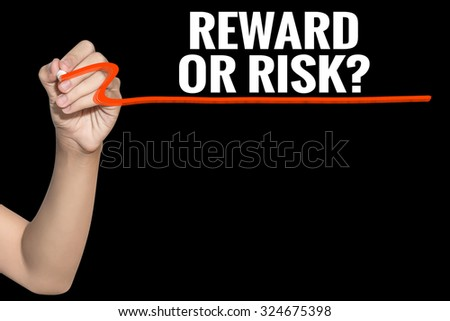 Reward or Risk word write on black background by woman hand holding highlighter pen - stock photo