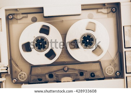 rewinding of vintage audio tape compact cassette, sepia tone with artistic film noise - stock photo