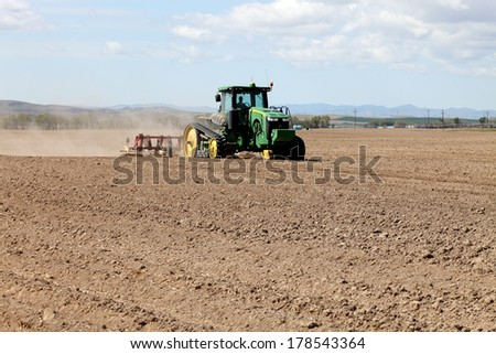Rexburg, Idaho, USA Apr. 11, 2012  Farm machinery plowing the ground in preparation for planting wheat in the fertile farm fields of Idaho.