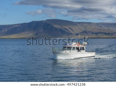 Reykjavik, Iceland - September 5 2016: The ferry travels to tiny Vigur Island across the fjord, Hestfjordur, popular tourist destination for birdwatching, Mountains of Esja, dominate the background