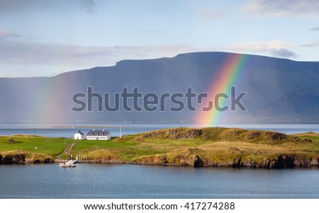 Reykjavik Landscape.  The view from Reykjavik harbour in Iceland as rain falls and a rainbow forms.  In the background is the Esja volcanic mountain range. - stock photo