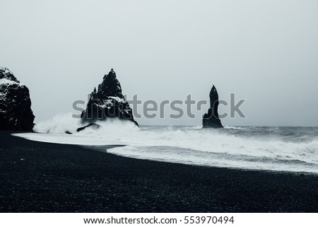 Reynisdrangar rock formations at black Reynisfjara Beach. Coast of the Atlantic ocean near Vik, southern Iceland. Slow shutter shot