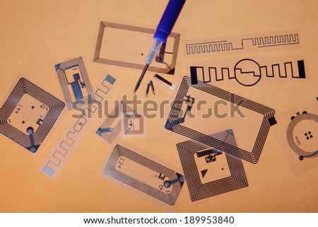 RFID. Radio Frequency Identification implantation syringe and chips on Radio Frequency Identification tags, orange background - stock photo