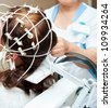 rheoencephalography - a doctor attaches electrodes on a patients head - stock photo