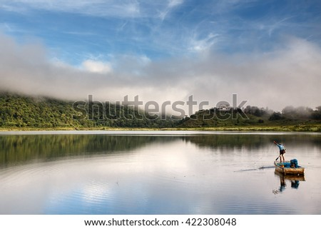 RHI LAKE, MYANMAR - JUNE 21 2015: Local fisherman on the daily fishing trip at the start of the monsoon season in the recently opened to tourists Chin State region of Western Myanmar (Burma) - stock photo
