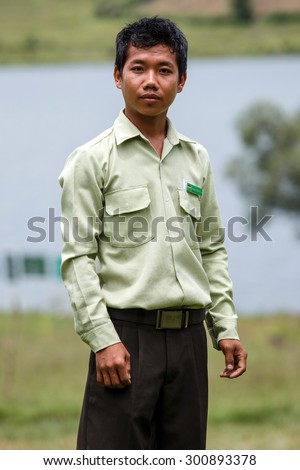 RHI, MYANMAR - JUNE 22 2015: Government Administration Official man wears smart green uniform in the recently opened region of Chin State in Western Myanmar (Burma) - stock photo