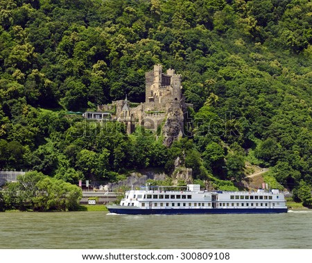 Rhine valley with cruise ship and castle Rheinstein, Germany. Rhine Valley is UNESCO World Heritage Site - stock photo