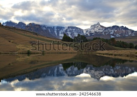 Rhino Horn peak in the Drakensberg National Park, South Africa, reflects in the waters of a lake. - stock photo
